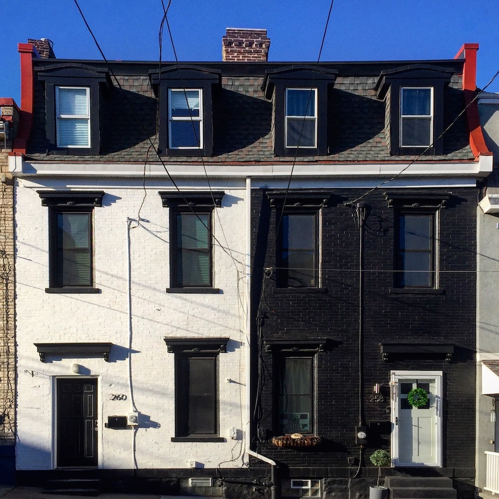 pair of matching row houses, one painted white, the other black