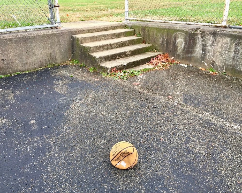 deflated basketball in empty lot