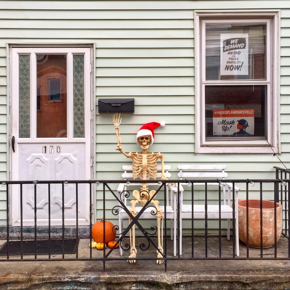 plastic skeleton on front porch with arm raised to wave hello