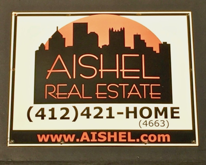 real estate for sale sign including logo with Pittsburgh skyline