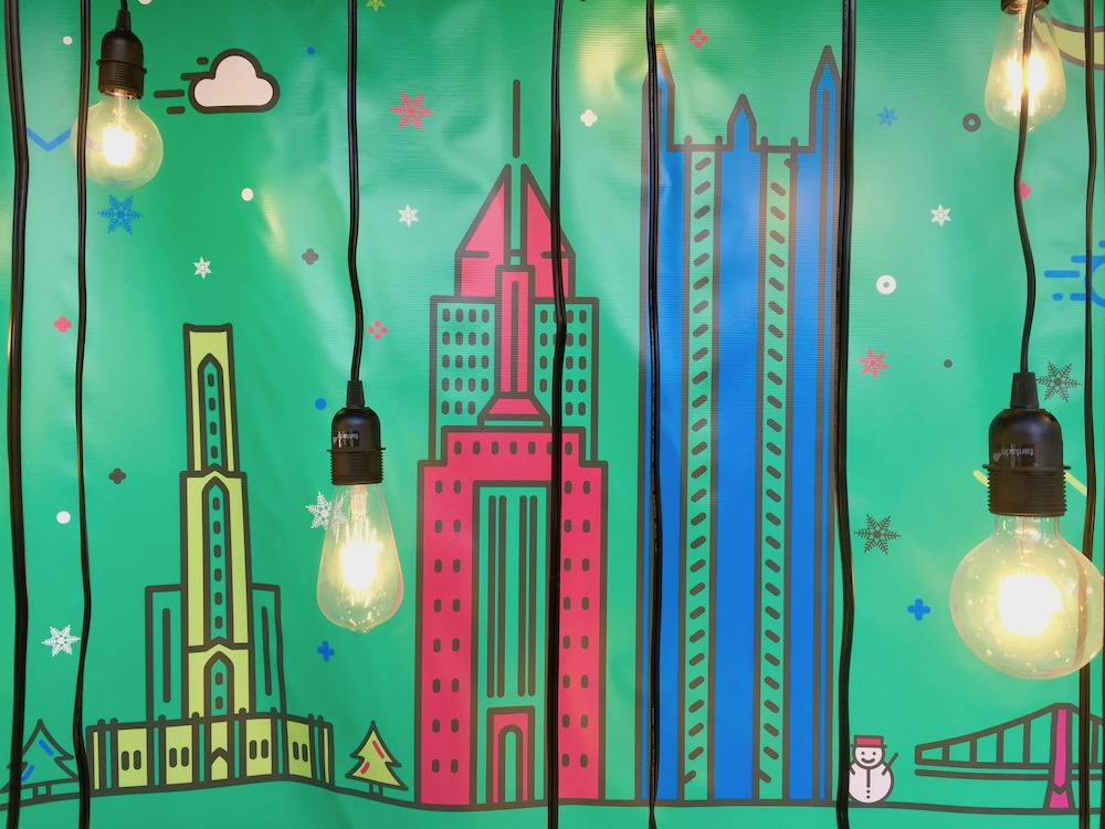 store window display of artist painted iconic buildings of Pittsburgh with light bulbs