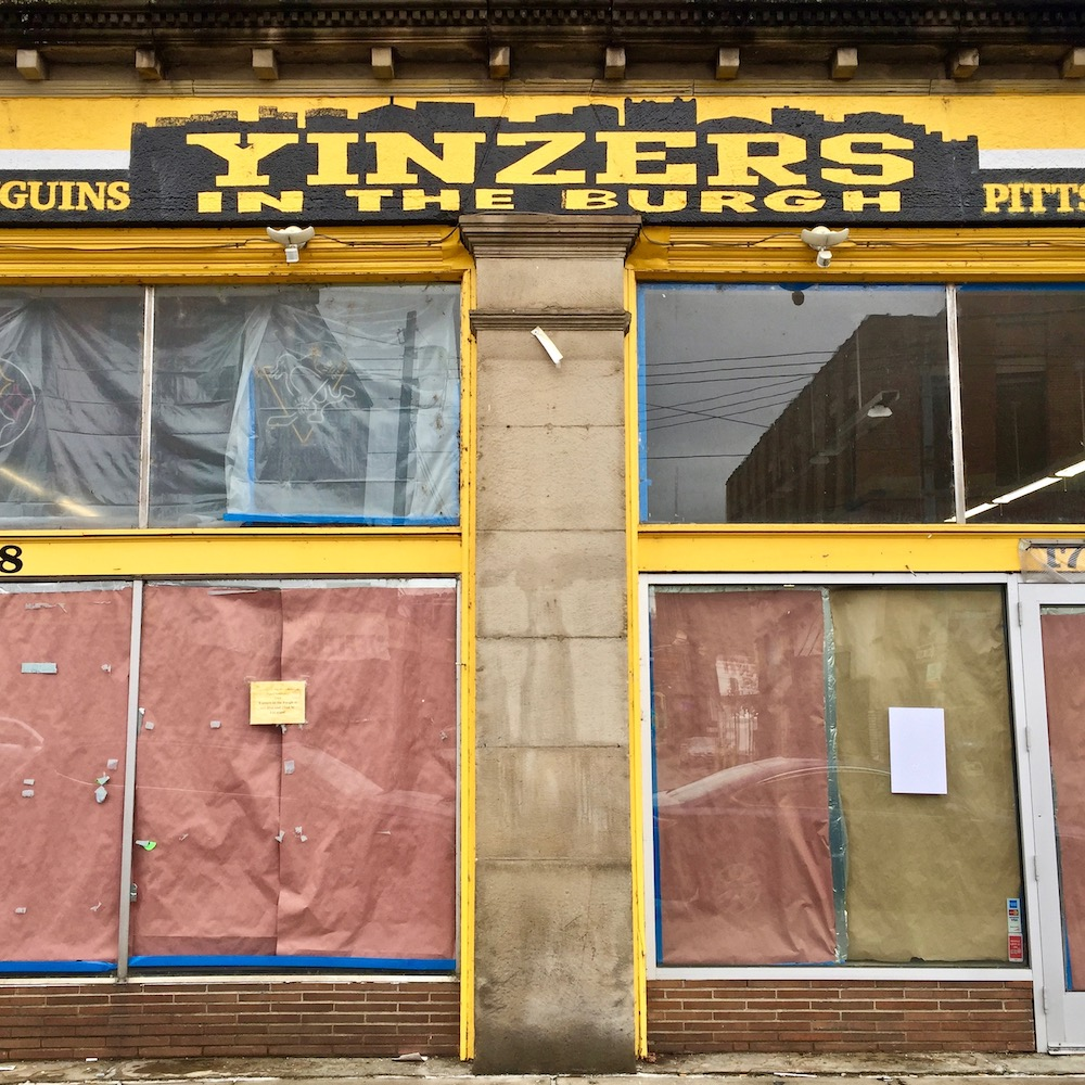 closed storefront of Yinzers in the Burgh with hand-painted Pittsburgh skyline