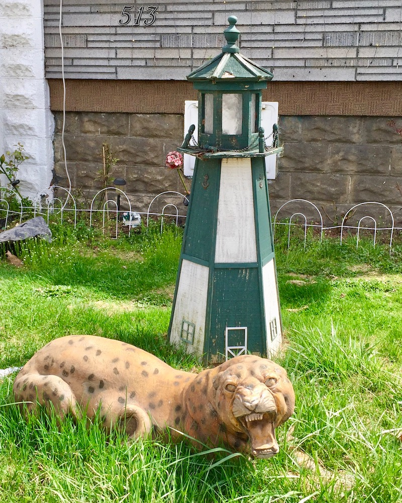lighthouse lawn ornament with leopard model in front yard of house