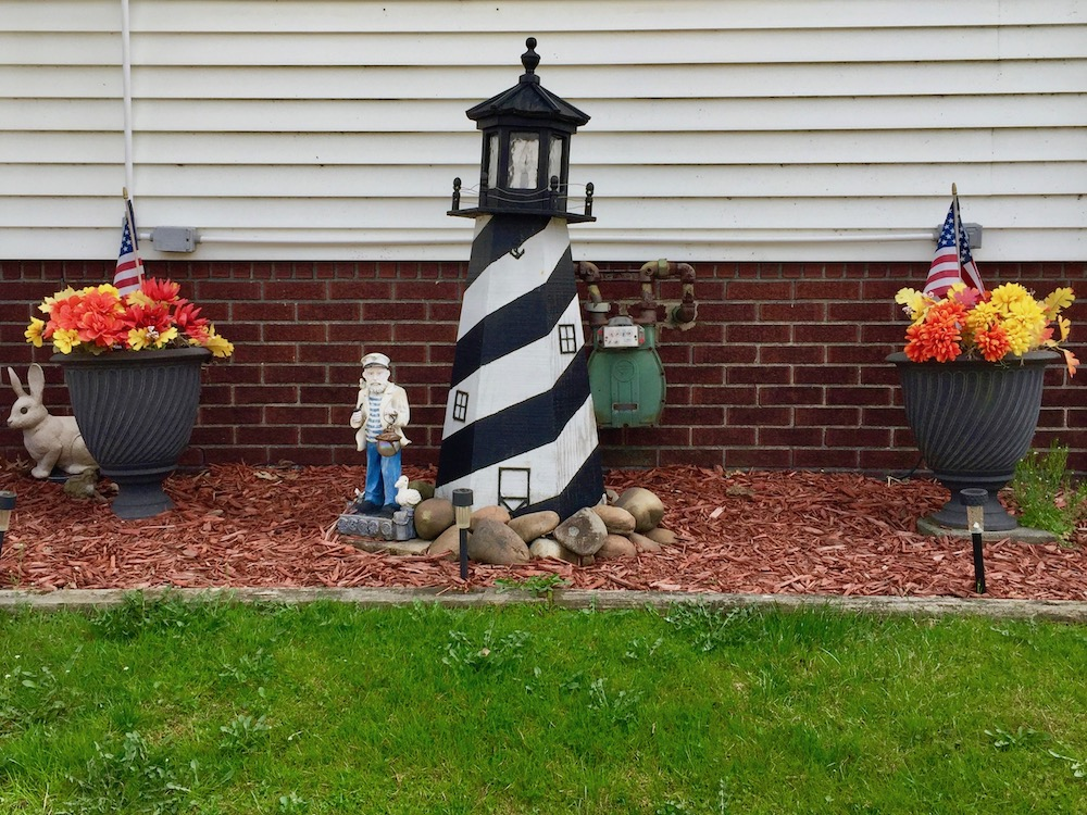 front yard decoration including potted flowers, lighthouse ornament and old sailor decoration