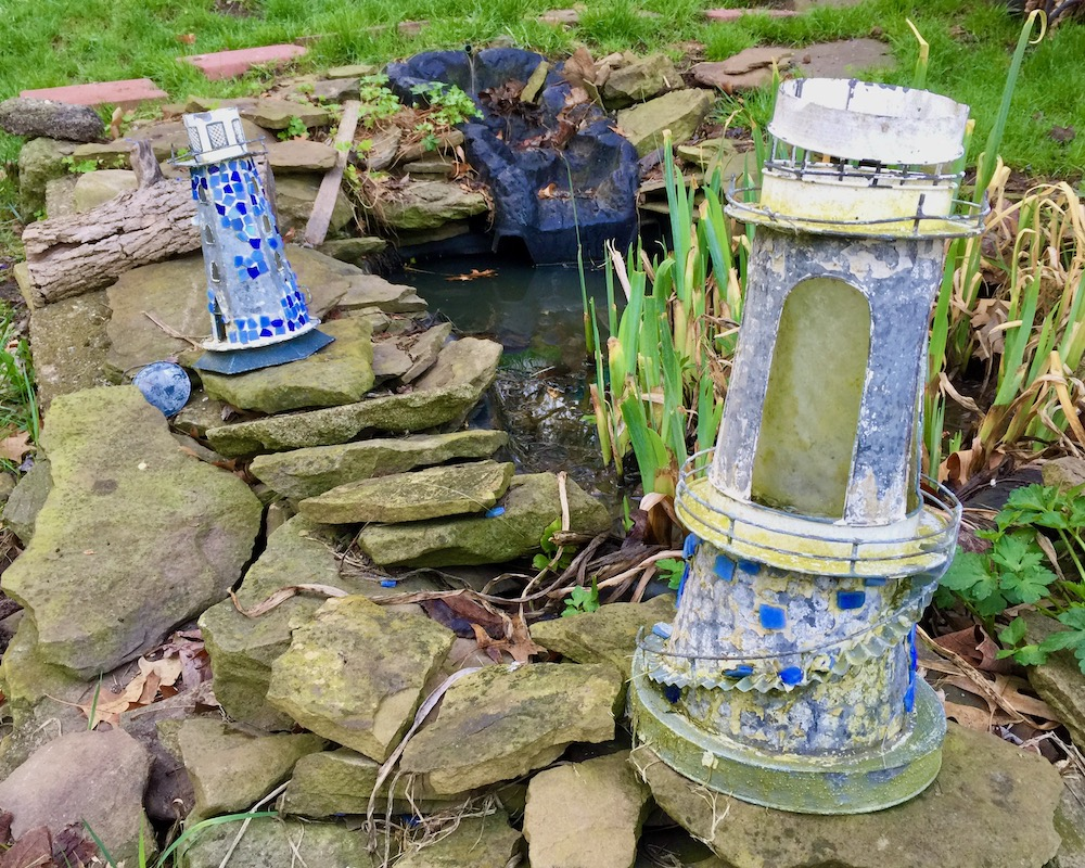 pair of ornamental lawn lighthouses by water garden feature