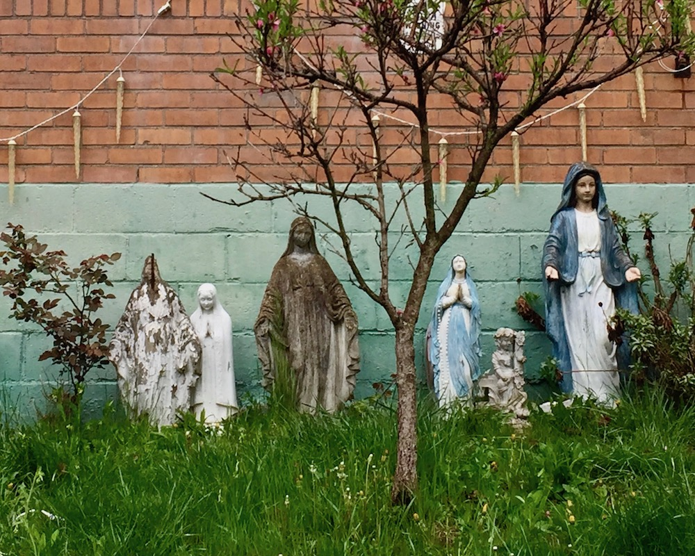 cinderblock and brick residential wall with five different statues of Mary