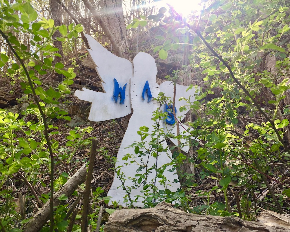 wooden cutout of angel placed on hillside