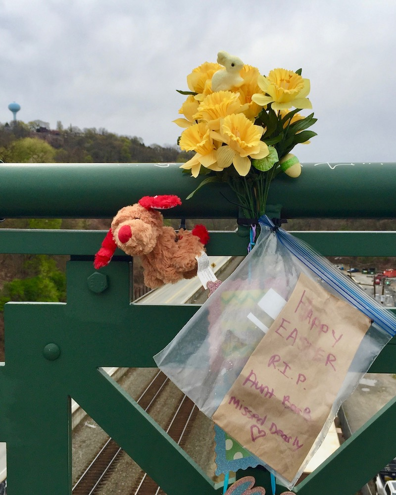 memorial display with flowers, stuffed animal, and letter on bridge railing