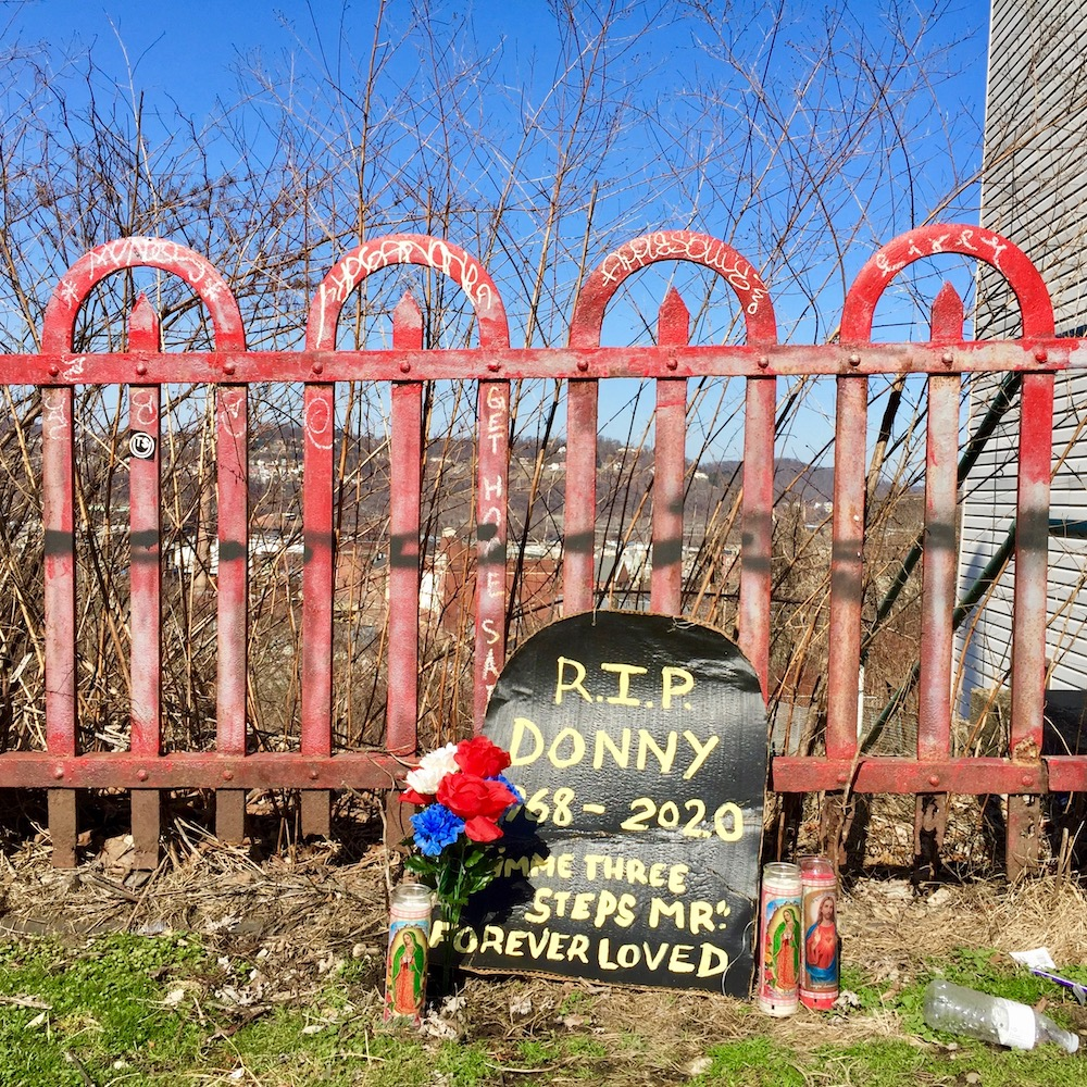memorial placed by iron fence with flowers and candles