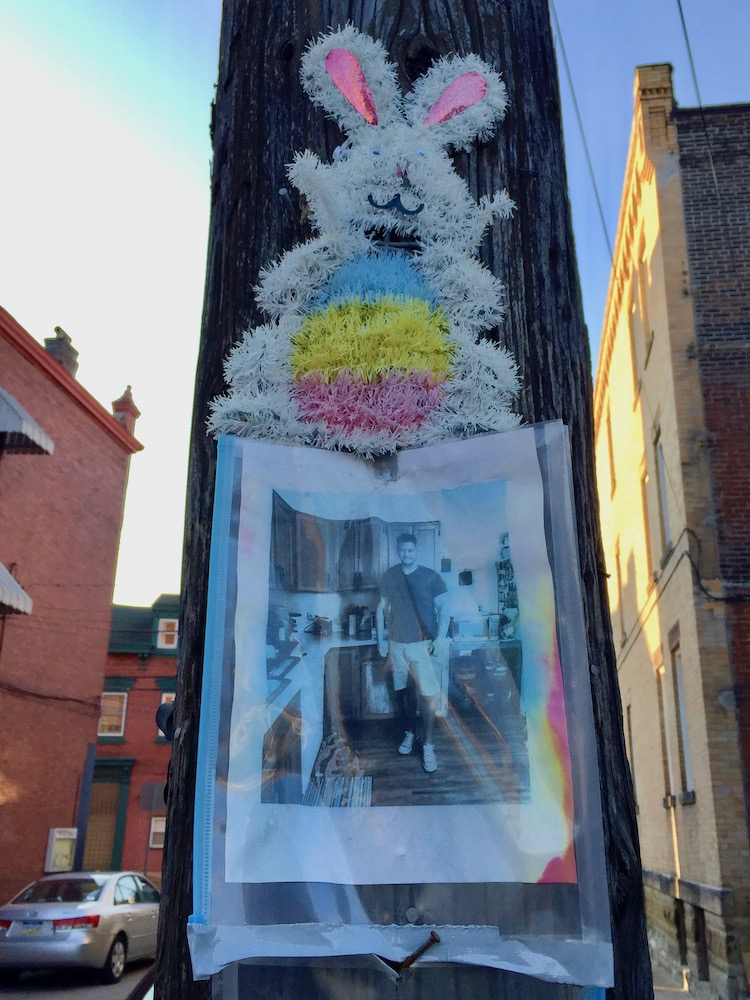 memorial featuring photograph and Easter bunny on utility pole