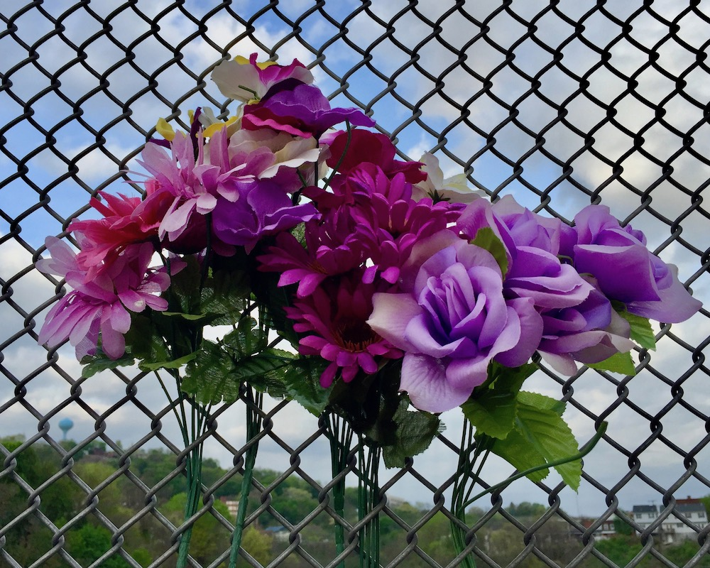 memorial flowers in chain link fence