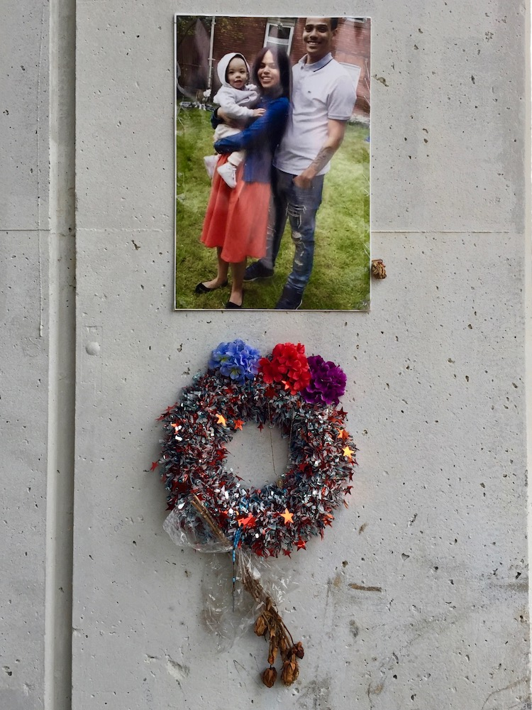 memorial featuring photograph of small family and sparkley wreath on cement wall