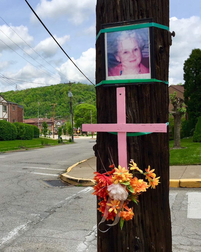 memorial featuring photograph, pink cross, and flowers on utility pole