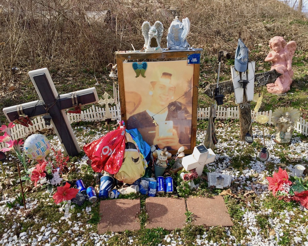 memorial for young man featuring large photograph, cross, figurines, and cans of Bud Light beer