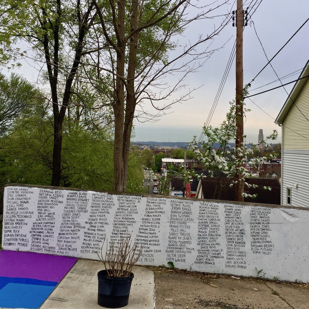 short wall painted white with names of many victims of police killings