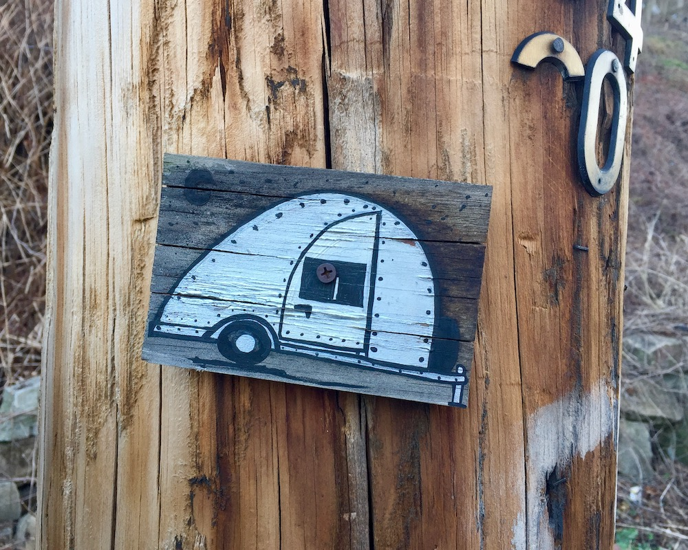 small painting of camper trailer on wood screwed to utility pole