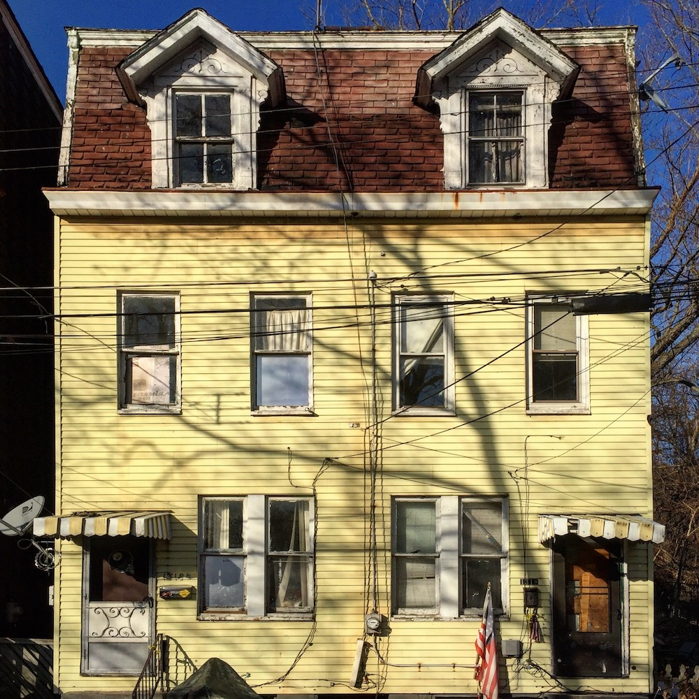 pair of row houses with matching yellow siding