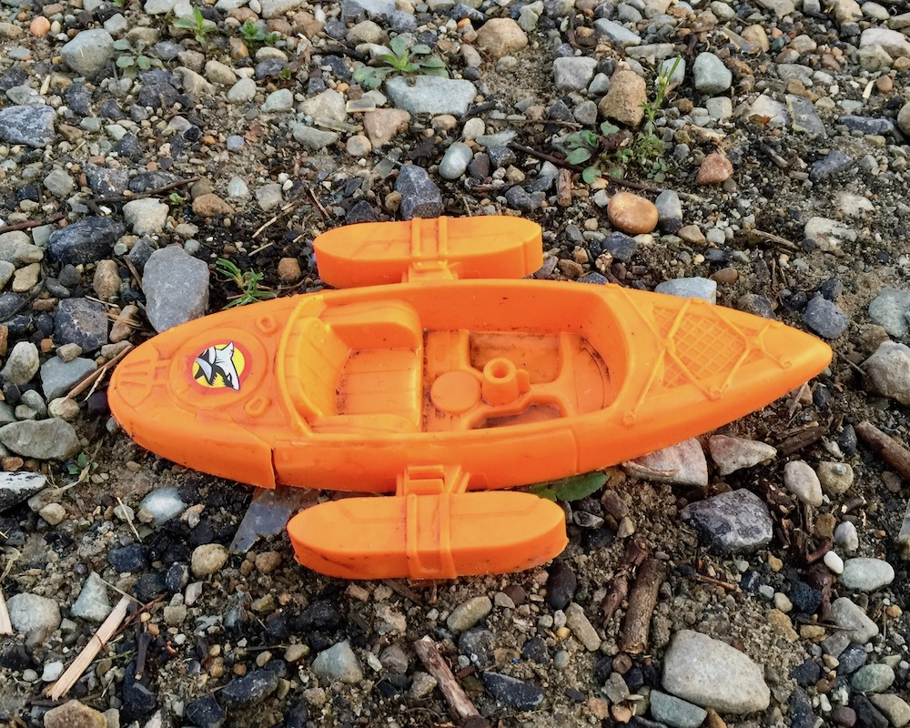 plastic toy boat crushed in gravel