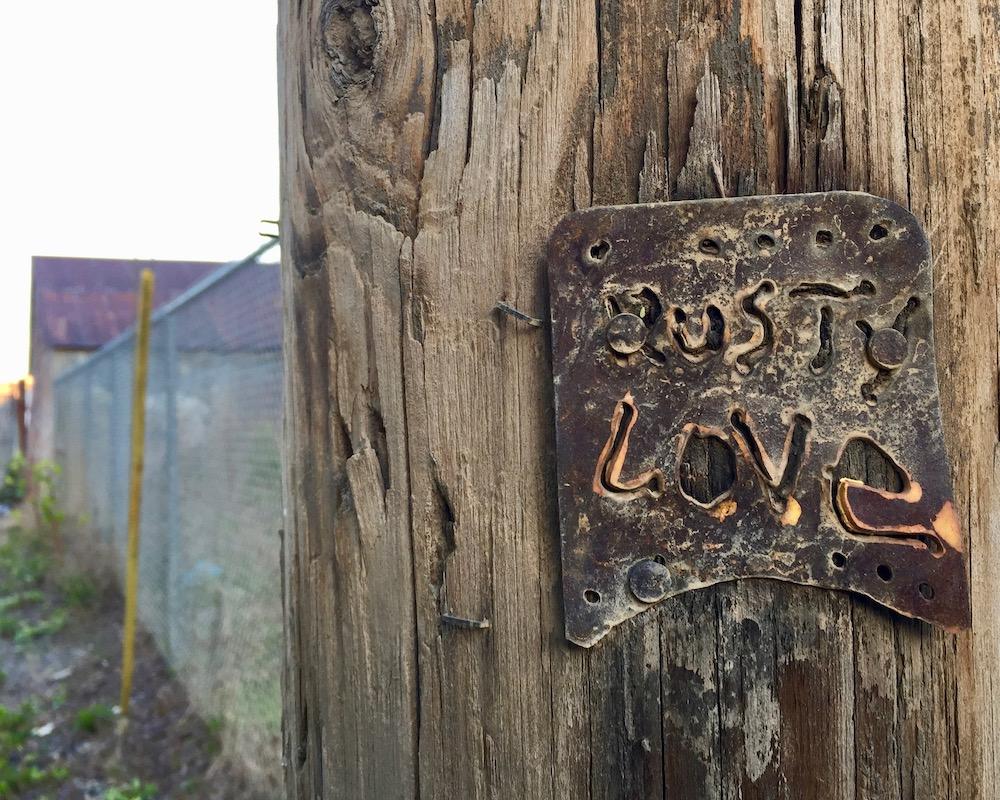 "metal piece with words ""Rusty love"" cut out nailed to utility pole"