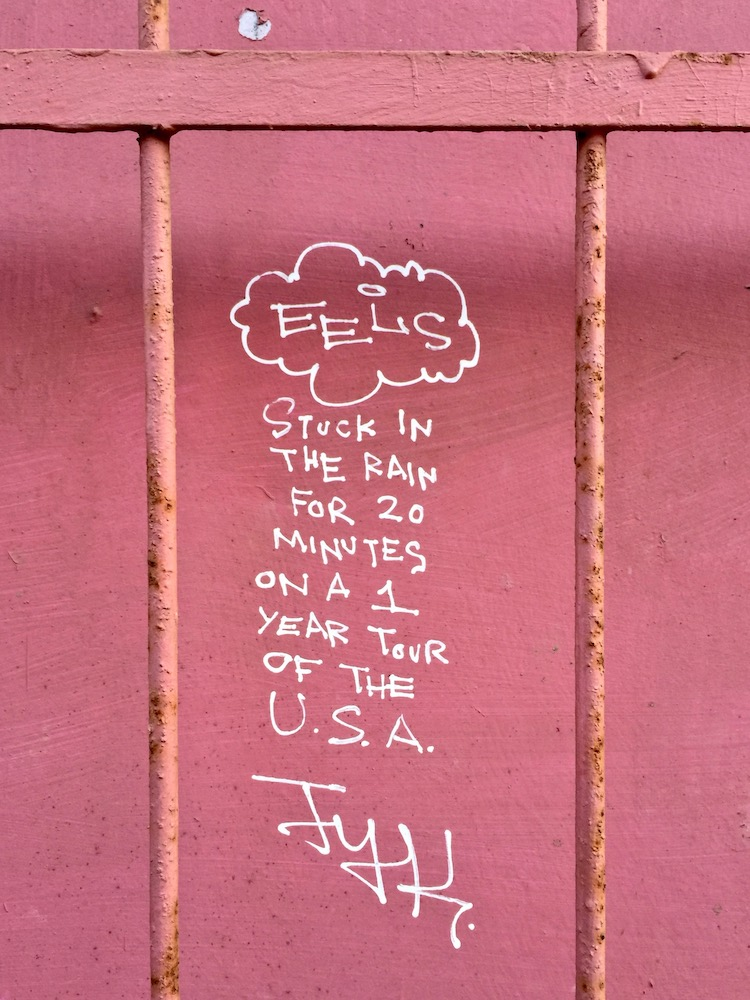 "graffiti on pink wall reading ""Stuck in the rain for 20 minutes on a 1 year tour of the USA"""