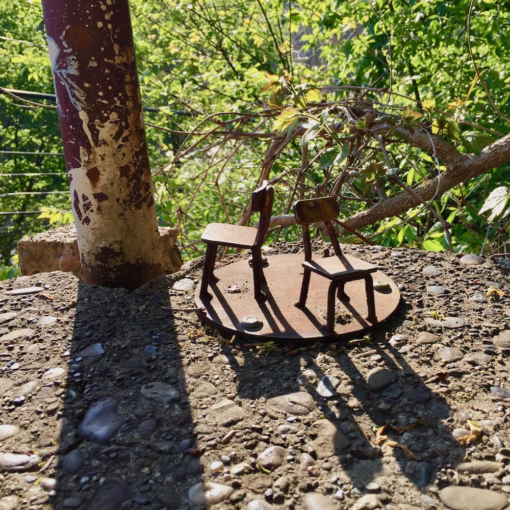 sculpture of two chairs anchored into public steps
