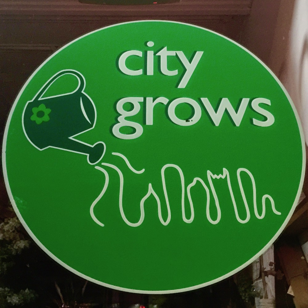 window sign for City Grows featuring downtown Pittsburgh buildings as growing grass