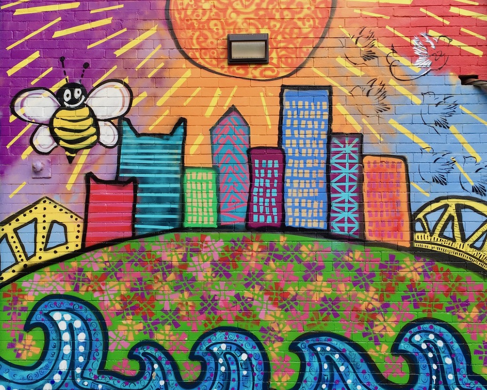 mural on brick wall featuring cartoon-like painting of downtown Pittsburgh