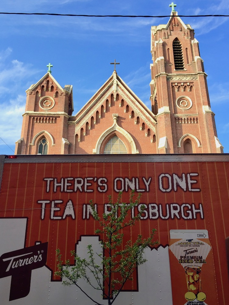 Turner's Tea van with graphics of the Pittsburgh skyline parked in front of ornate church