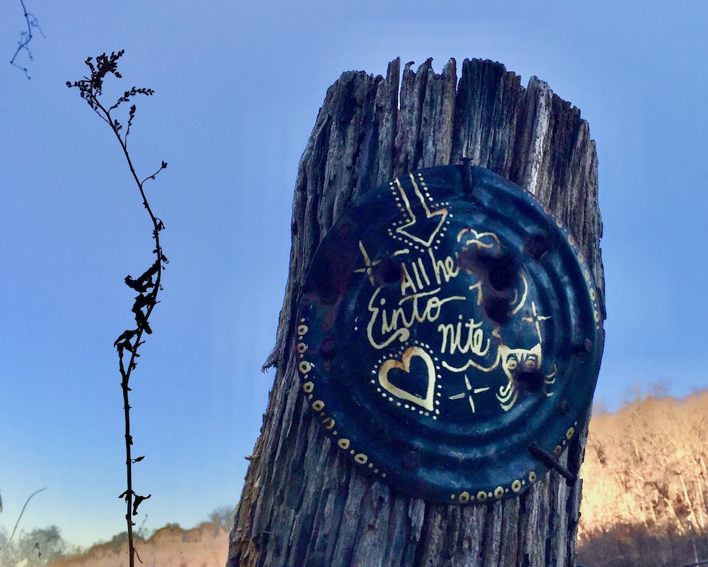 painting on tin can nailed to utility pole