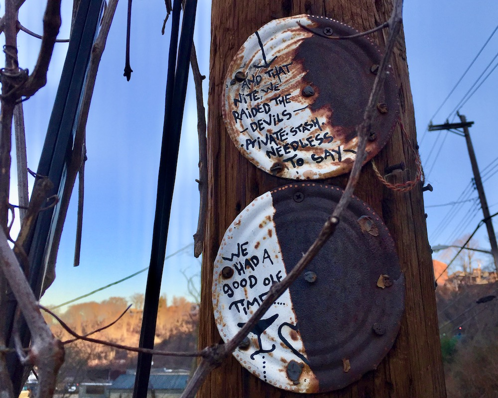 rusted paintings on tin can nailed to utility pole
