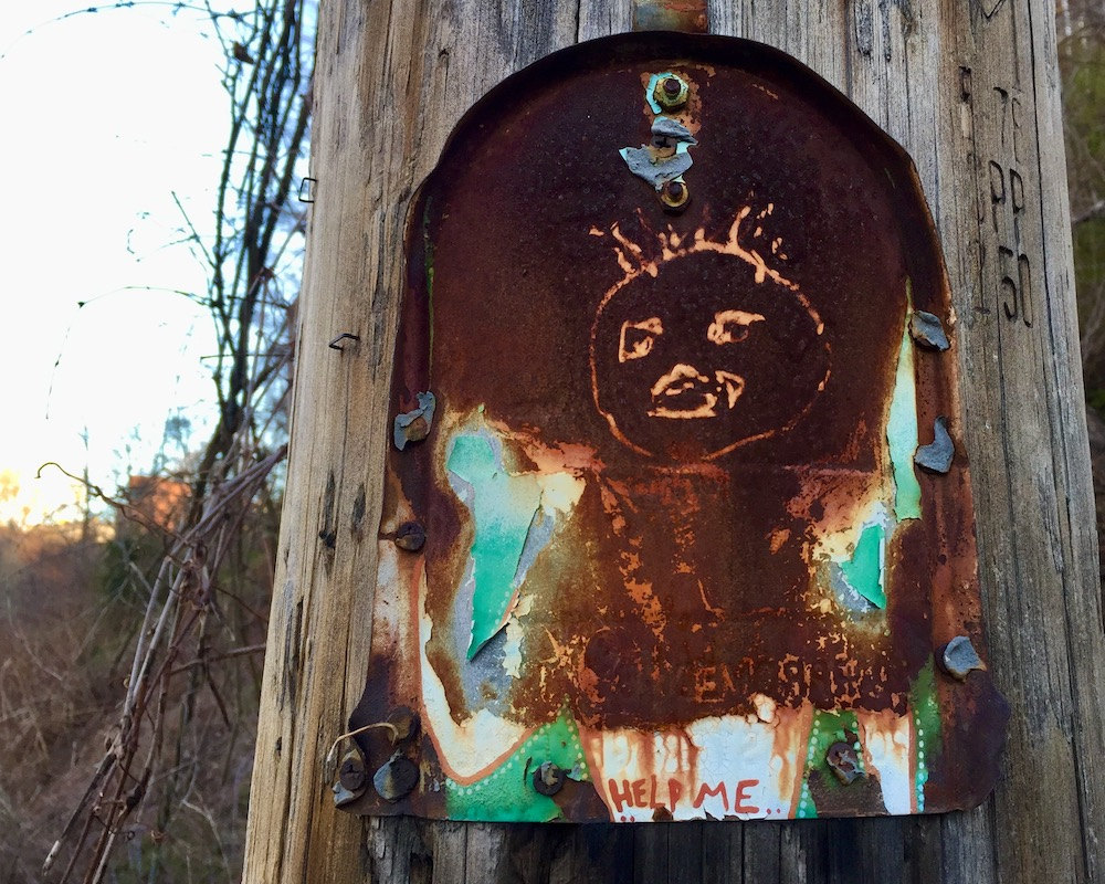 rusted painting on tin can nailed to utility pole
