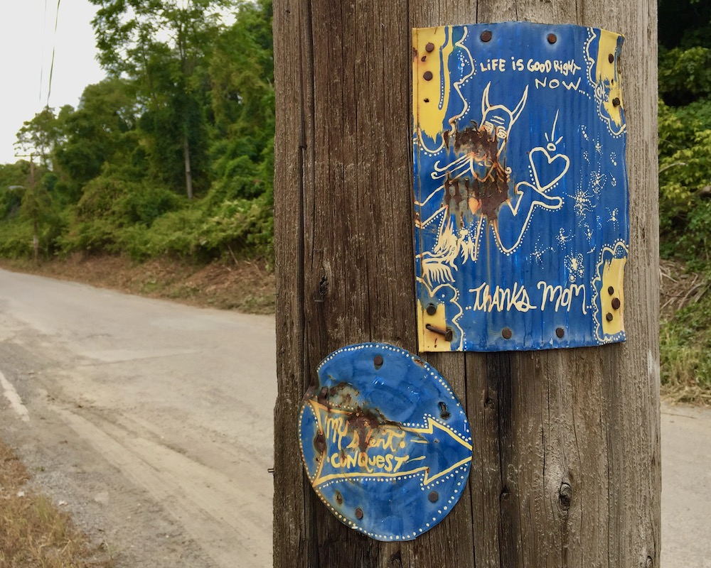 paintings made from flattened tin cans nailed to a utility pole