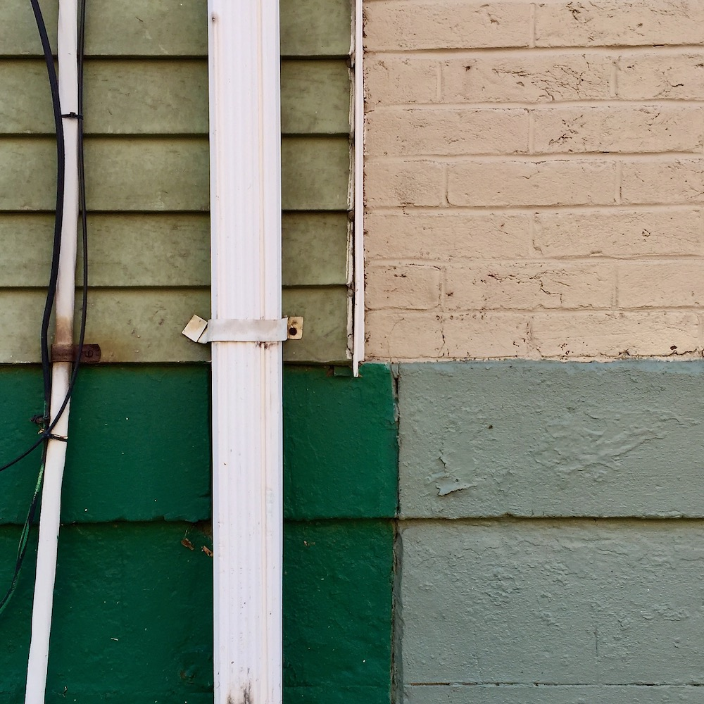 wall surface with geometric shapes formed by paint colors, siding, drain pipe