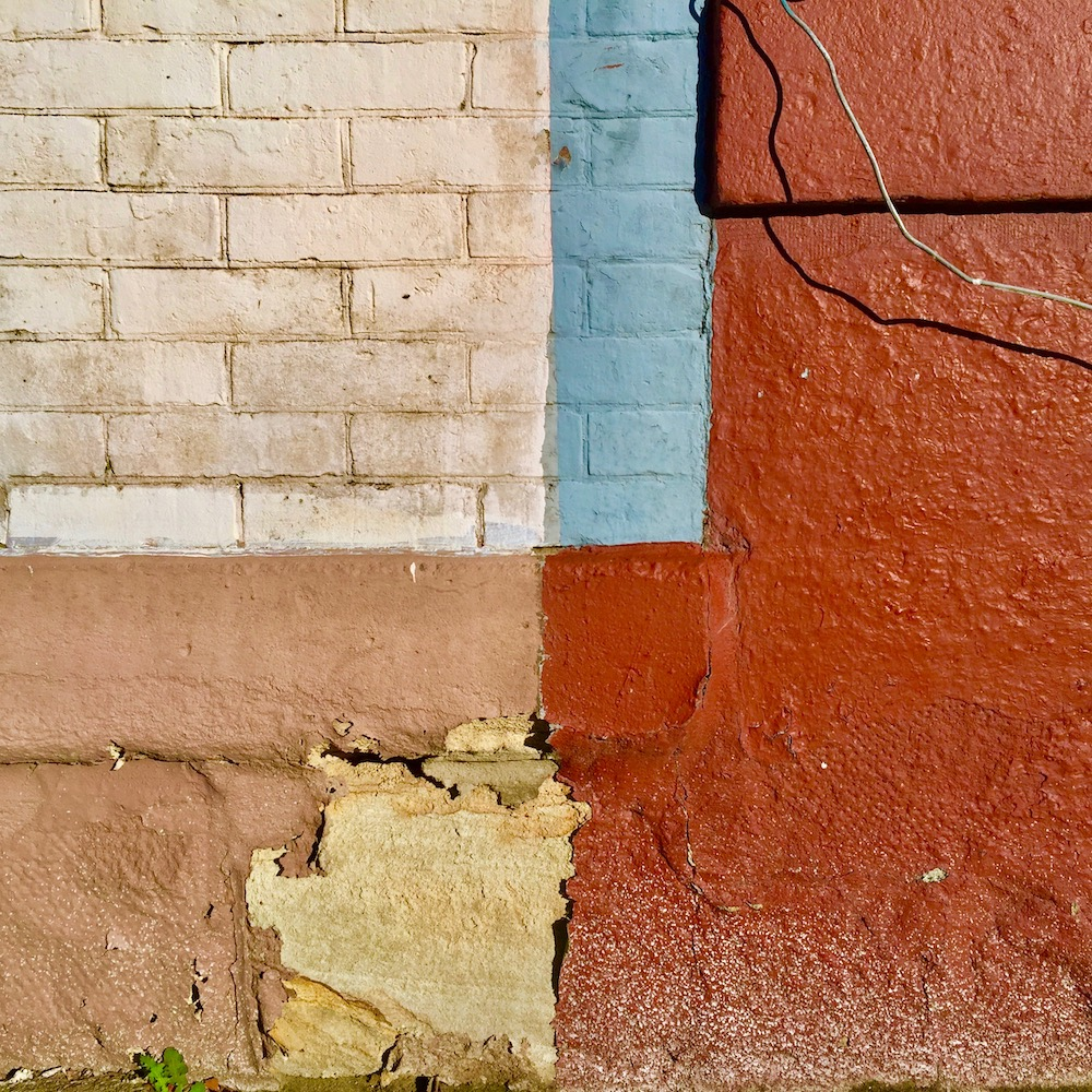 brick exterior wall of row house painted in multiple sections