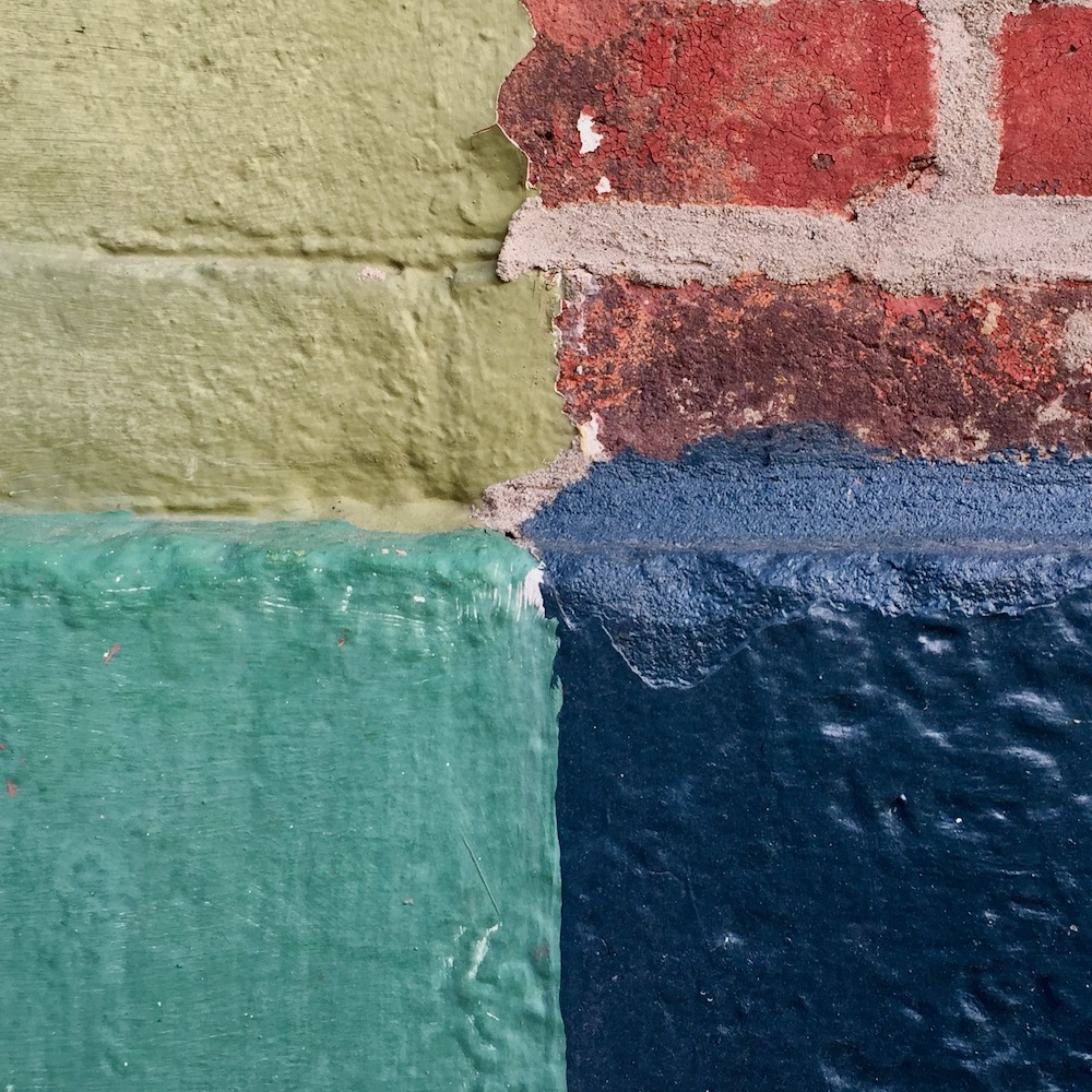 detail of painted row house walls and foundation showing distinct square quarters of different shapes and colors