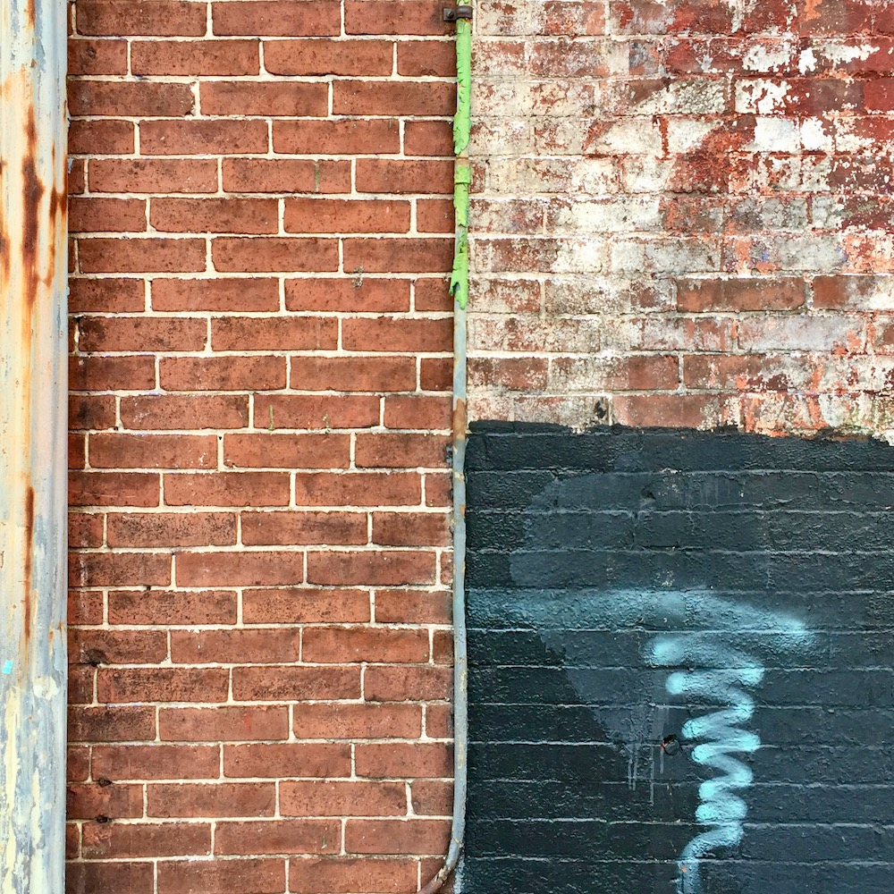 detail of brick wall where different paint layers have made distinct geometric sections