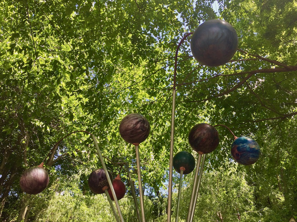 sculpture with many bowling balls on long rods