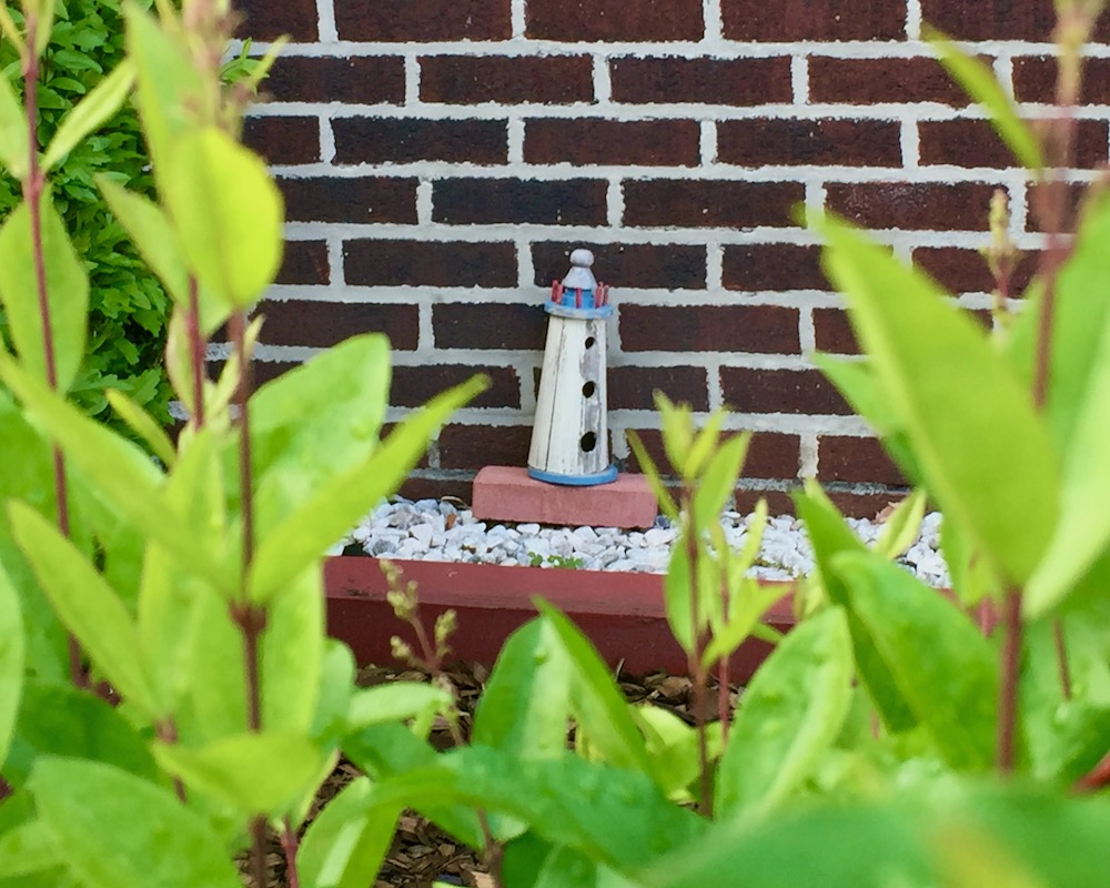 small wooden lighthouse decoration in front of brick house
