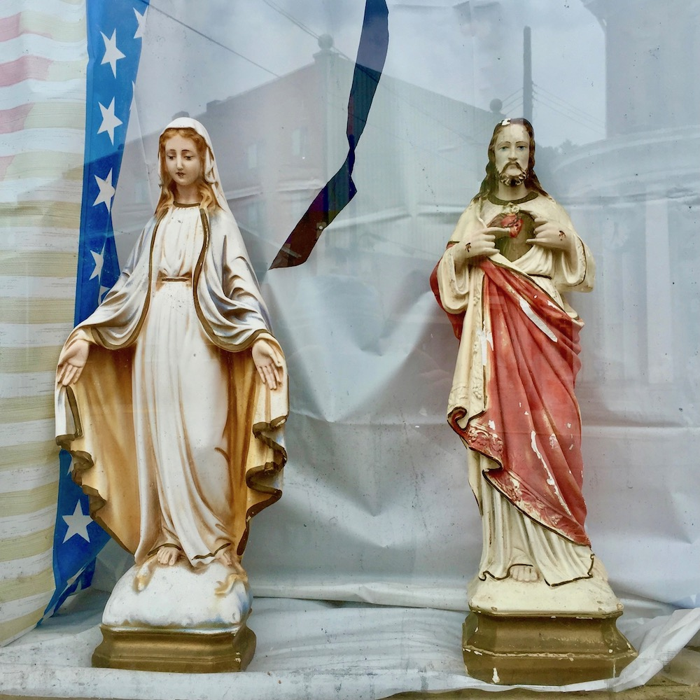 statues of Mary and Jesus in glass storefront window