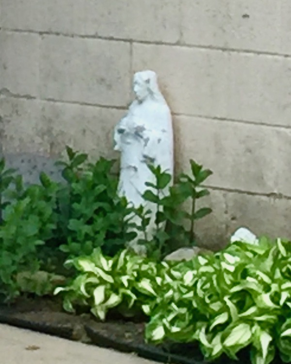 statue of Mary against a cinderblock wall