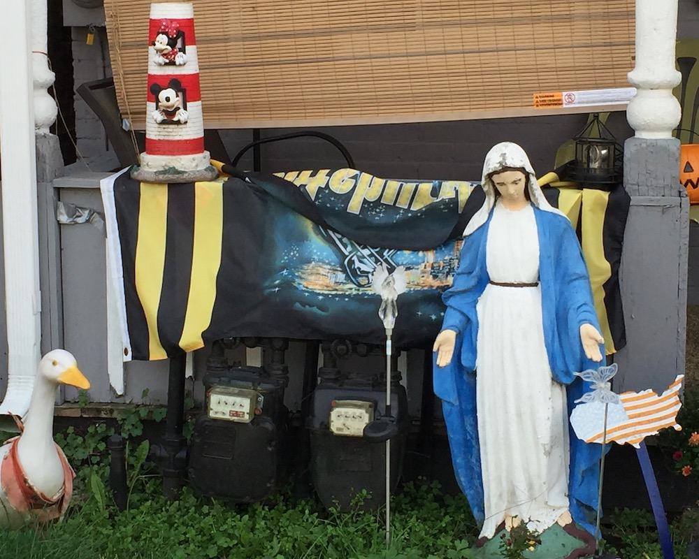 small yard and porch decorated with statue of Mary, goose, Disney lighthouse, Steelers flag
