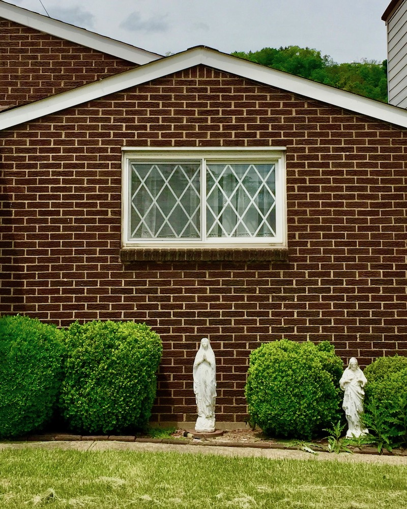 ceramic statue of Mary in front of brick house