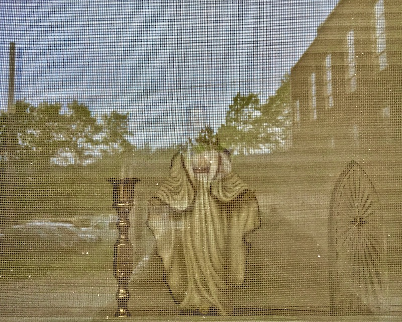 statue of Mary in screen window