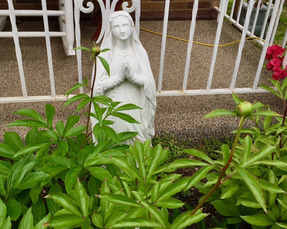 statue of Mary between flower garden and front porch
