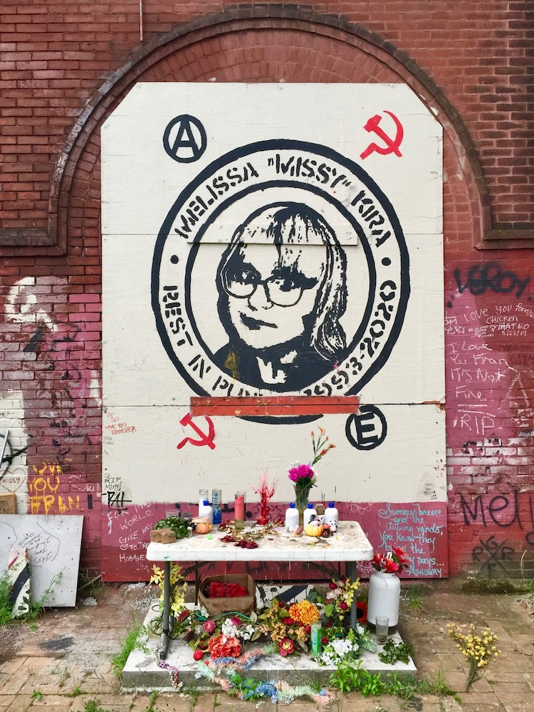memorial portrait painted on brick wall with candles and flowers below
