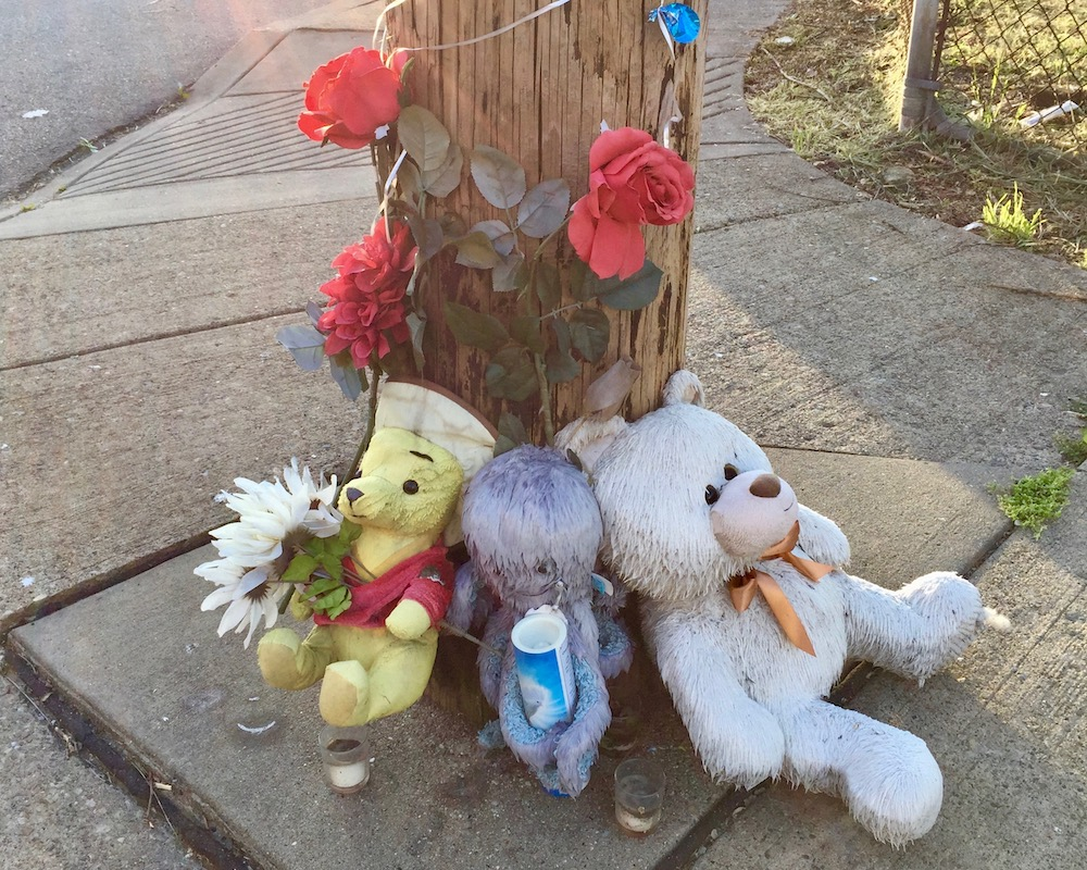 roadside memorial including stuffed animals, candles, and plastic flowers