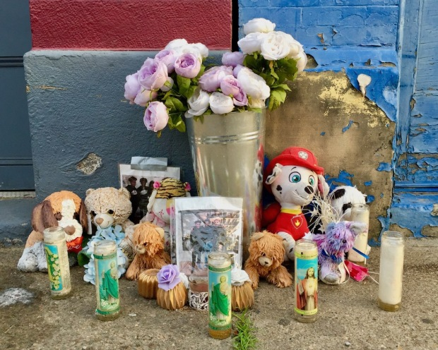sidewalk memorial with photos, flowers, candles, and stuffed animals