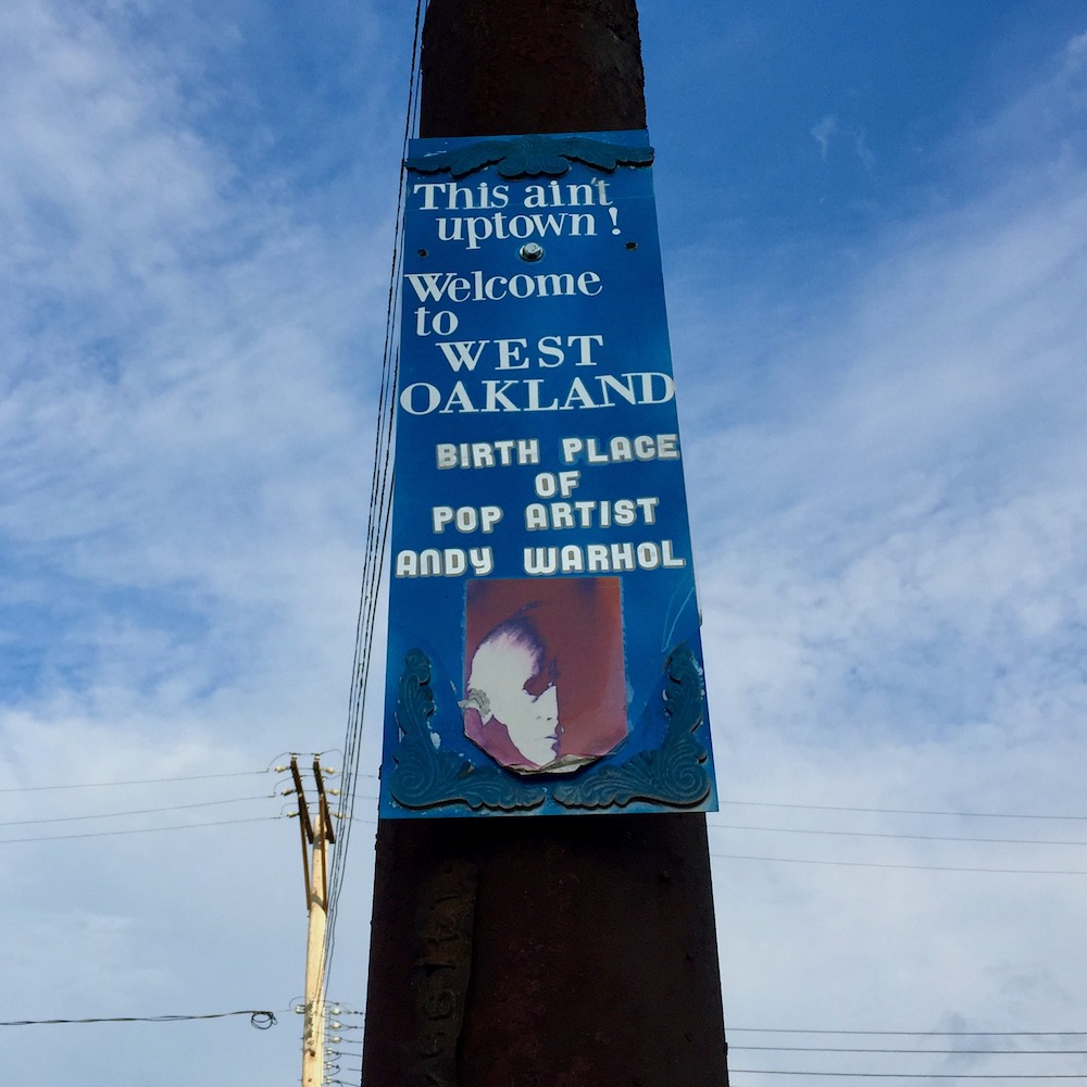 """sign for West Oakland neighborhood of Pittsburgh reading """"This ain't Uptown! Welcome to West Oakland: birthplace of pop artist Andy Warhol"""""""