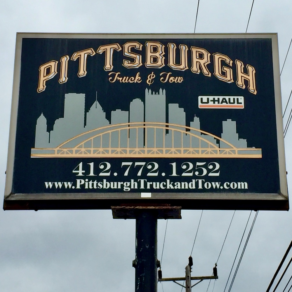 sign for Pittsburgh Truck & Tow including silhouette of the downtown Pittsburgh skyline