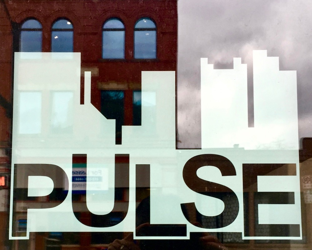 window sign for Pulse including abstracted downtown Pittsburgh skyline